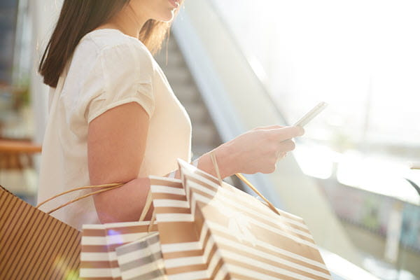 Woman with shopping bags looking at phone.