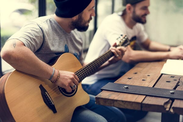 Man holding guitar sitting with another man.