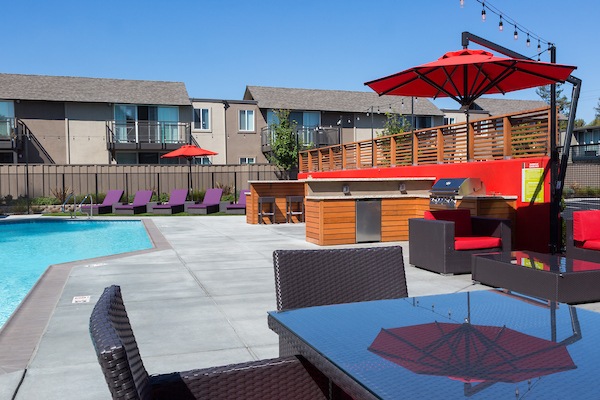 Outdoor swimming pool area surrounded by BBQ area, bar seating, lounge chairs, and umbrellas.