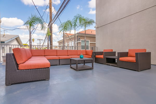 Community courtyard with a table, lounge seating, and a neighborhood view from balcony.