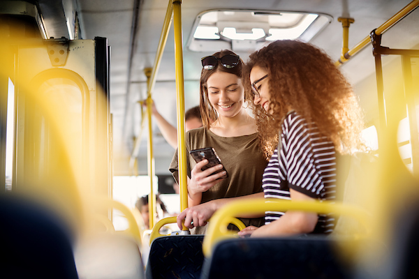 Two women on bus looking at a phone.