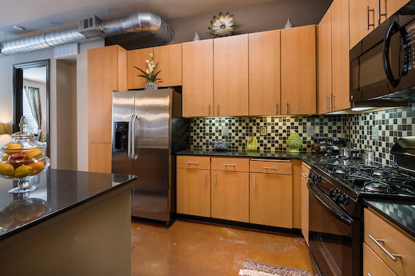 Staged kitchen with stainless steel appliances, a gas stove, granite countertops, and polished concrete flooring.