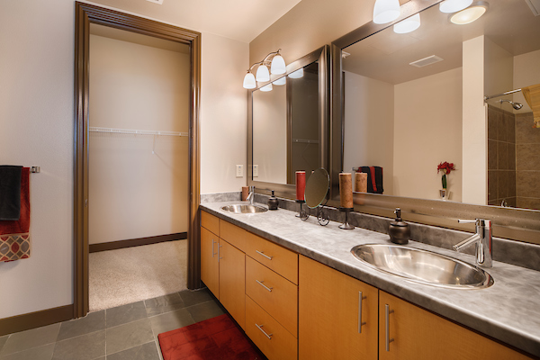 Staged bathroom with granite countertops and tile flooring.