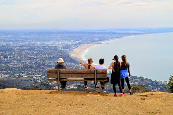Hiking group near bench overlooking city and large body of water.