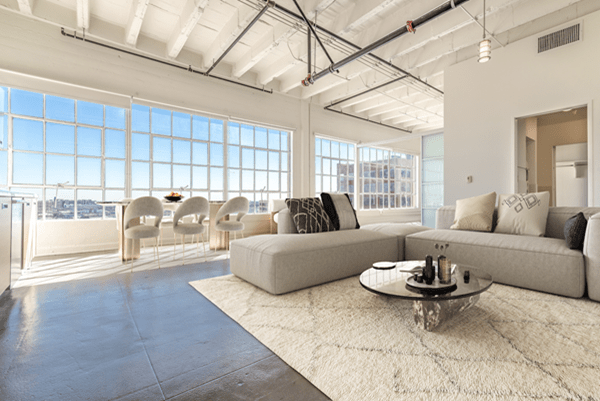 Open kitchen with stainless steel appliances and large windows featuring exposed ducts, polished concrete floors, and tall ceilings.