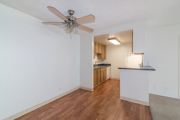 Kitchen adjacent to dining area with ceiling fan.