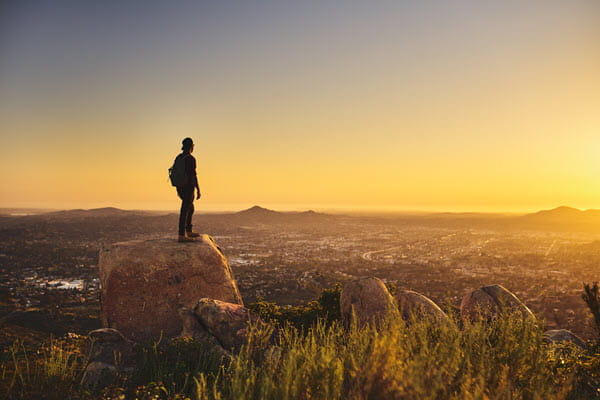Man on peak of mountain overlooking city at sunset.
