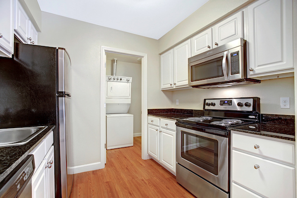 Kitchen with stainless steel appliances and hardwood-style vinyl flooring