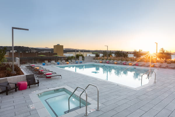 Outdoor spa and swimming pool area with sundeck and lounge seating at sunset.