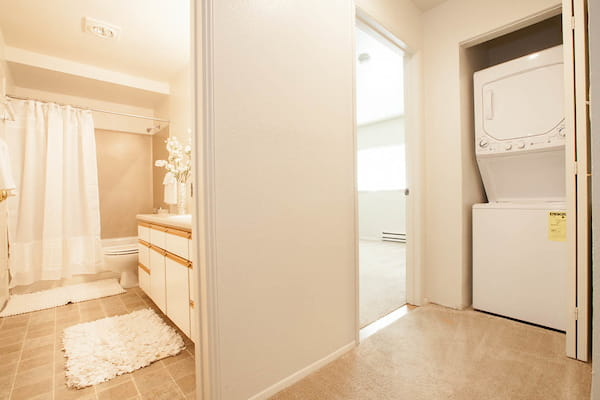 Hallway with bathroom and in-unit washer and dryer