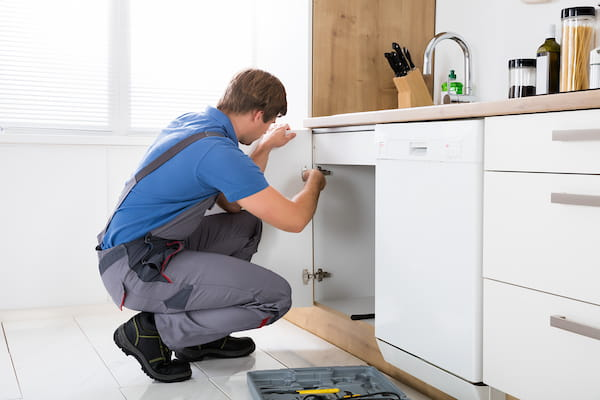 Maintenance person fixing a sink.