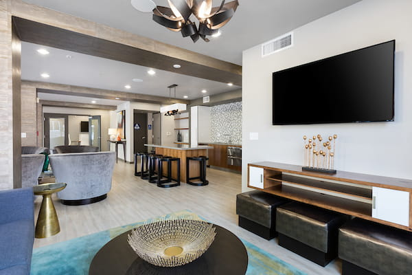 Clubhouse with kitchen, island, dining seating, TV, and hardwood style flooring.