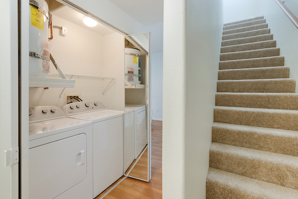 In-home washer and dryer unit adjacent to carpeted stairs.