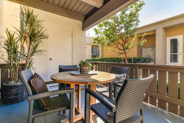 An apartment home balcony with table, chairs, and plants.