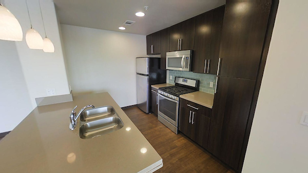 Kitchen with stainless steel appliances and breakfast bar.