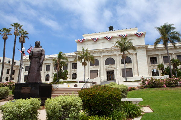 Exterior of San Buenaventura City Hall with palm trees and statue.