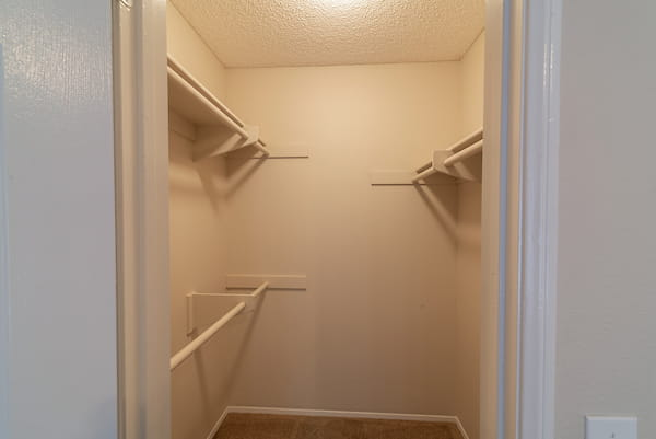 Walk-in closet with shelving and rack.