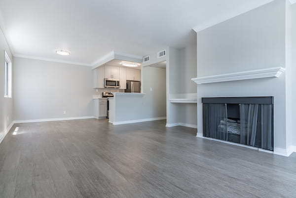 Living room with fireplace adjacent to kitchen.