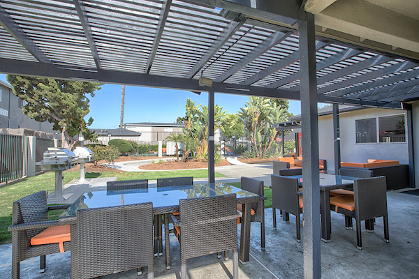 Community courtyard with tables and chairs under pergola.