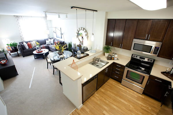 Kitchen with stainless steel appliances and breakfast bar adjacent to staged living room.