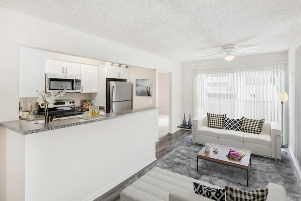 Kitchen with stainless steel appliances overlooking staged living room.