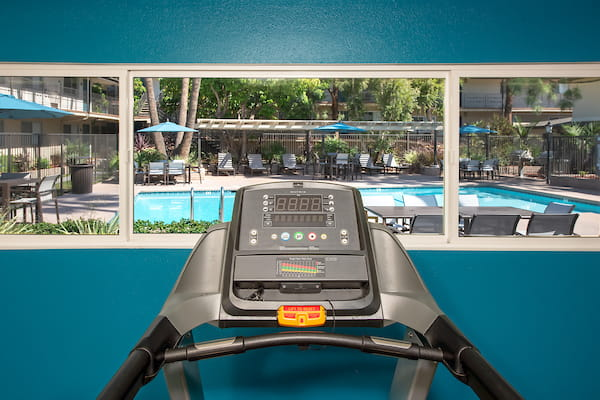 View of outdoor swimming pool area from fitness center's treadmill.