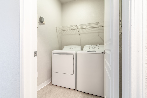 In-home washer and dryer unit with shelving.