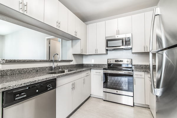 Modern galley kitchen with hardwood-style vinyl flooring and stainless steel appliances.