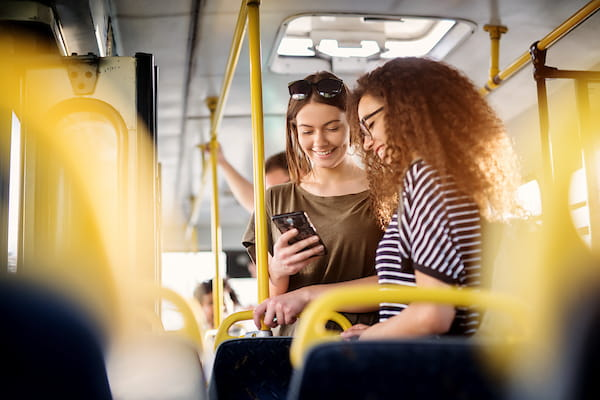 Two women on bus looking at phone.
