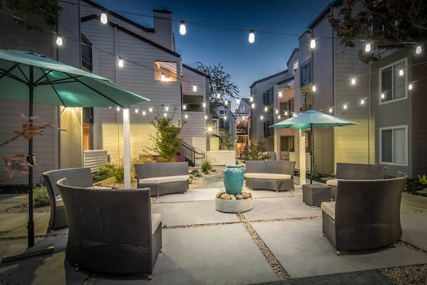 Community courtyard with a fountain, lounge seating, and umbrellas at dusk.