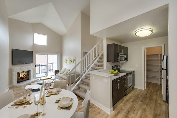 Staged living and dining area with vaulted ceiling, hardwood style vinyl flooring and stairs. Kitchen with stainless steel appliances and quartz counter tops.