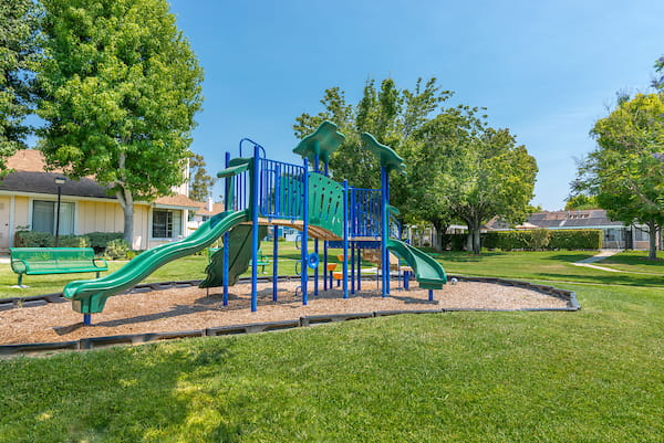 Playground with a climbing wall and slide surrounded by mulch and grass.