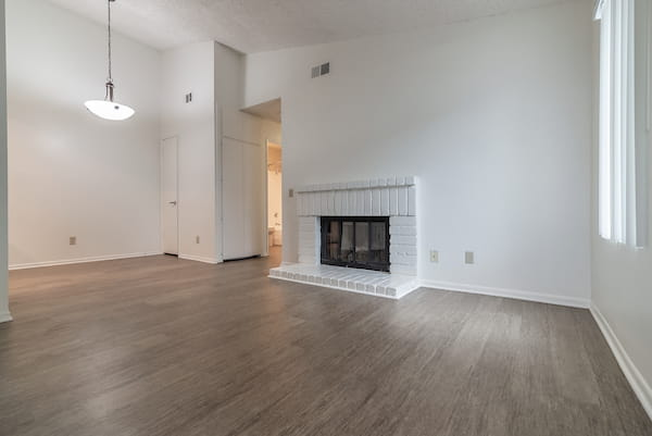 Living room with fireplace and hardwood-style vinyl flooring.