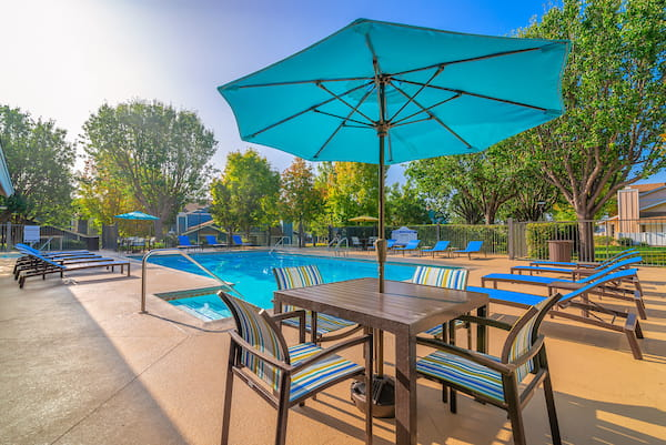Outdoor swimming pool area with tables, chairs, and umbrellas, surrounded by trees.