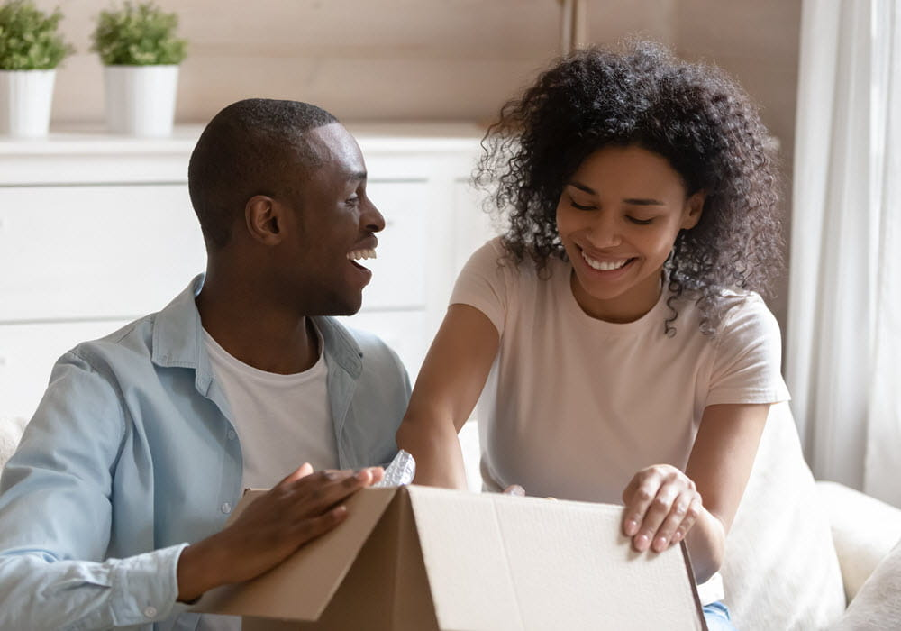 Smiling couple packing belongings in a moving box.