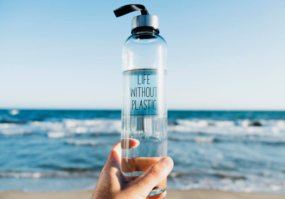 Person at the beach holding a reusable water bottle.