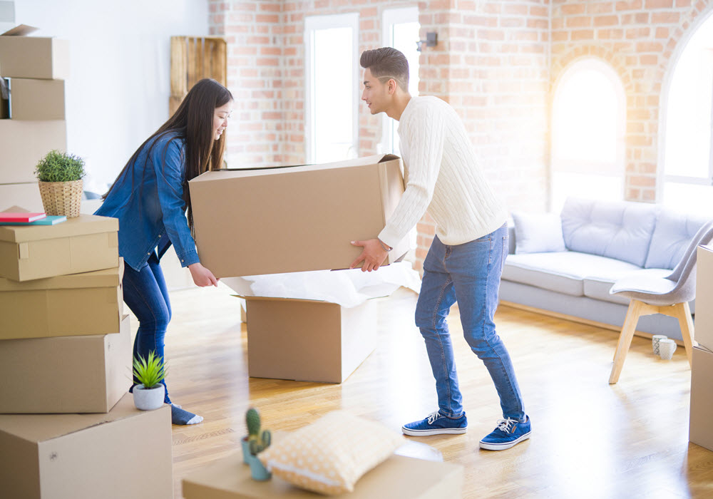 Couple in an apartment with moving boxes.
