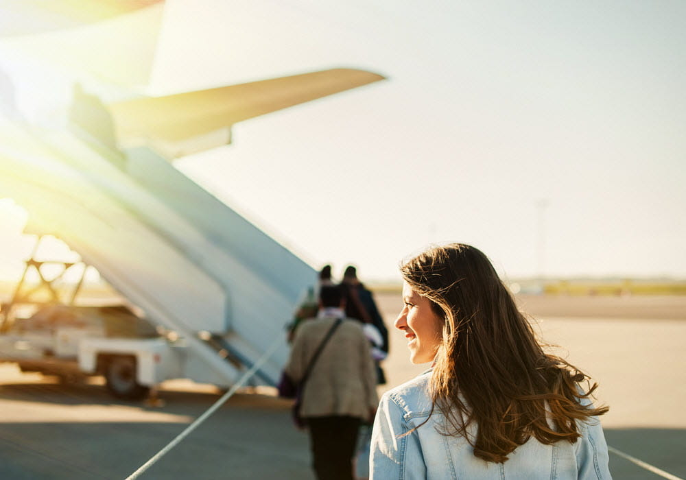 Woman boarding plane at the airport.