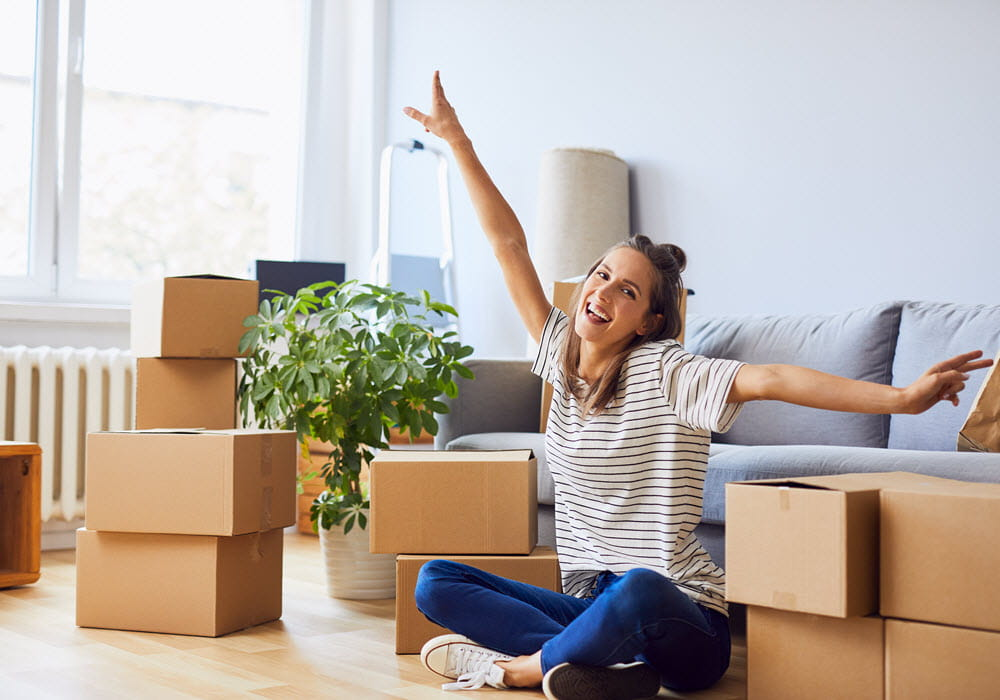 Happy young woman in apartment with moving boxes.