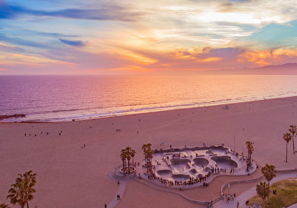 Venice Beach at sunset with view of ocean and skate park.