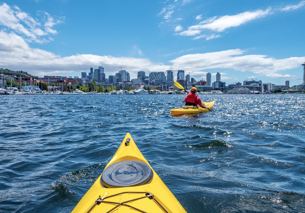 Kayaks on Lake Union in Seattle, Washington with skyline in the background.