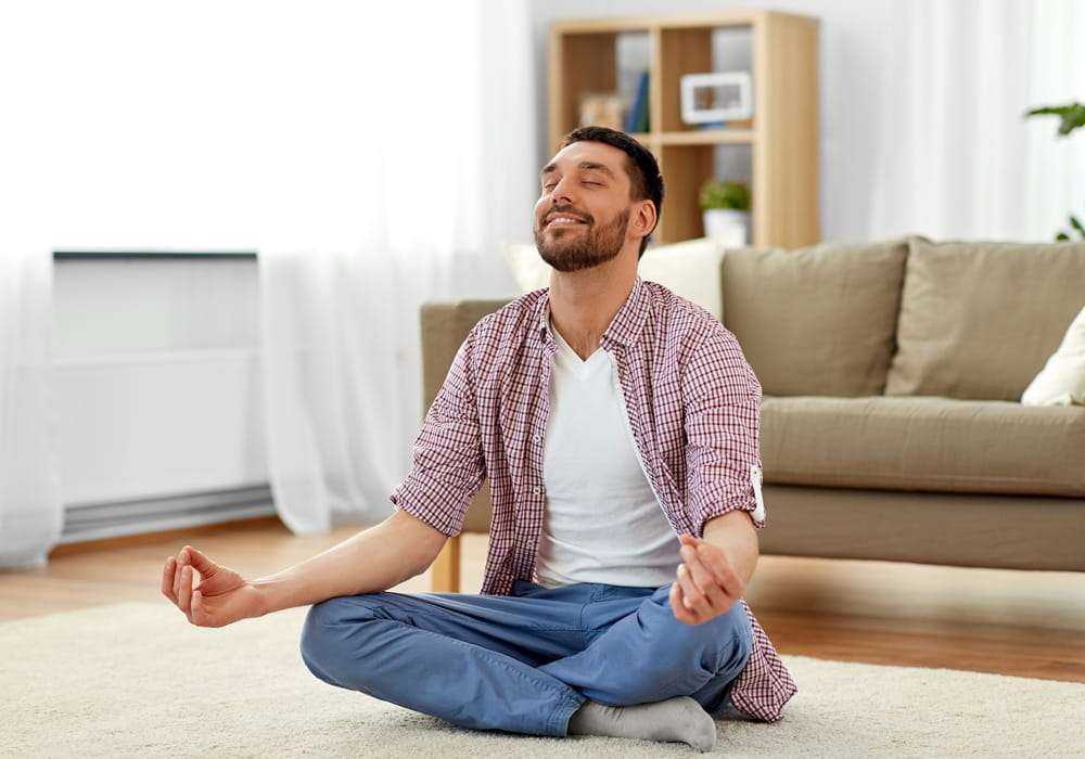 Man relaxed and meditating in his apartment living room