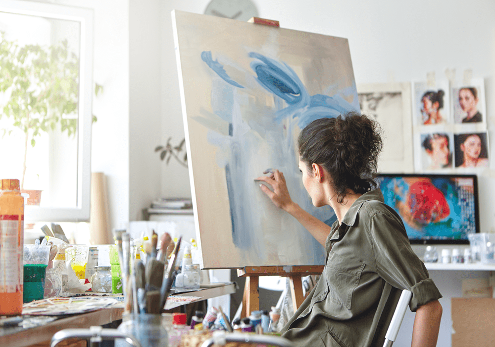 Woman practices her new painting hobby in her apartment home.