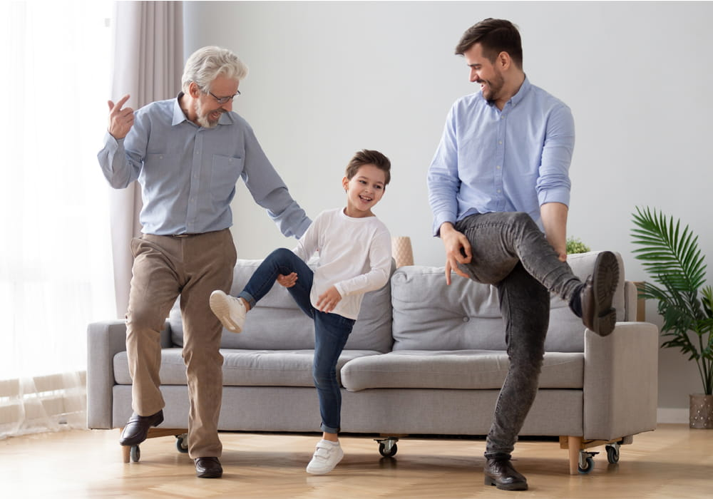 Grandfather, father, and son dancing together in their West Coast apartment home living room.