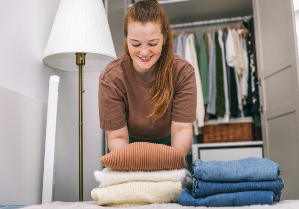 Woman folding and organizing clothes into closet.