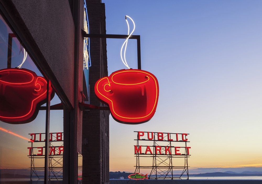 Red coffee shop sign near the Public Market in Seattle at dusk.