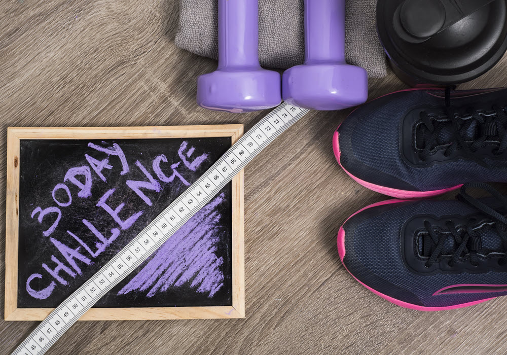 Staged 30-day challenge chalk board surrounded by fitness products.