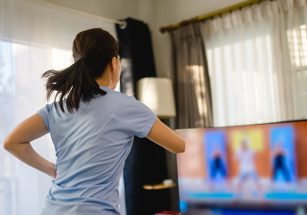Woman following a workout routine on her television in apartment.