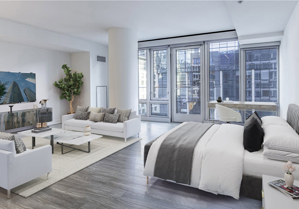 500 Folsom's staged studio apartment featuring bed, sofas, and a tv.