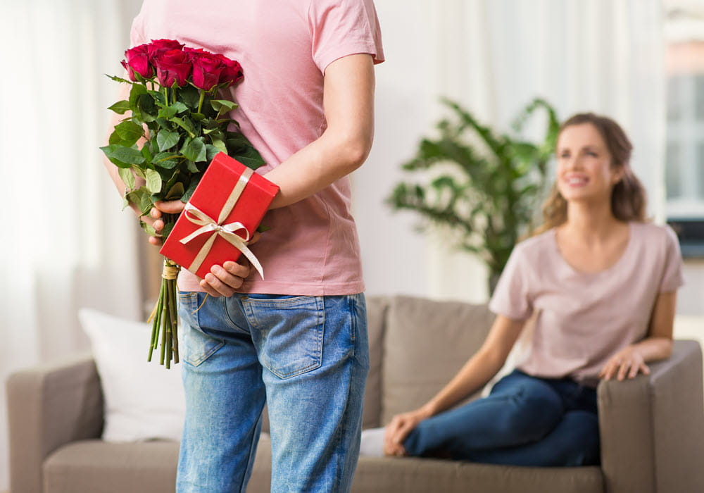 Man surprising woman with Valentine's Day gifts in apartment home.